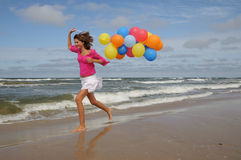 Teenager playing with balloons on the beach Stock Photo