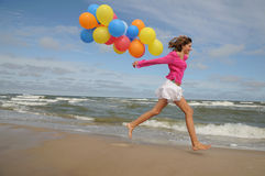 Teenager playing with balloons on the beach Royalty Free Stock Photos