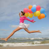 Teenager playing with balloons on the beach Royalty Free Stock Photo