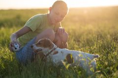 Teenager playing with a dog in the nature, stock photography