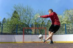 Teenager playing football rabona. Young man kicks the ball into the goal rabona royalty free stock photo
