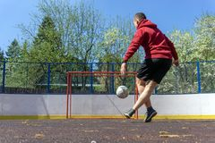 Teenager playing football rabona. Young man kicks the ball into the goal rabona royalty free stock image