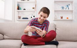 Teenager playing games on smartphone. With excitement while sitting on comfortable couch at home Stock Images