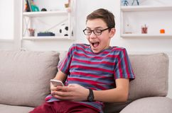 Teenager playing games on smartphone. Winner in online competition, sitting on comfortable couch at home Royalty Free Stock Image