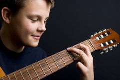 Teenager playing guitar. Portrait of teenager playing acoustic guitar, black background Stock Images