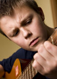 Teenager playing guitar. Portrait of teenage boy playing classical guitar Stock Image