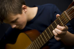 Teenager playing guitar. Portrait of teenager playing acoustic guitar Royalty Free Stock Images
