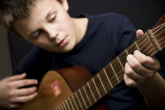Teenager playing guitar. Portrait of teenage boy playing classical guitar Stock Images