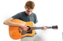 Teenager Playing Guitar. Young white teenager playing an acoustic guitar isolated on white Royalty Free Stock Photography