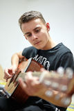 Teenager playing guitar. Closeup of a teenage boy playing his acoustic guitar Stock Photography