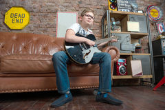 Teenager playing guitar. Male teenager sitting at home and playing guitar Royalty Free Stock Photos