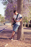 Teenager playing guitar. Near a tree Royalty Free Stock Photos