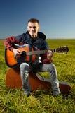 Teenager playing guitar outdoor. Teenage boy playing guitar outdoor in a grass field Stock Image