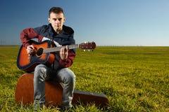 Teenager playing guitar outdoor. Teenage boy playing guitar outdoor in a grass field Royalty Free Stock Photos