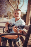 Teenager playing guitar. In the park Royalty Free Stock Photography