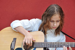 Teenager playing guitar in the street Royalty Free Stock Photos