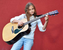 Teenager playing guitar in the street Royalty Free Stock Image