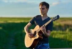 Teenager playing guitar at sunset. Teenage boy playing guitar at sunset in a wheat field Stock Image