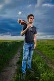 Teenager playing guitar at sunset. Teenage boy playing guitar at sunset in a wheat field Stock Photos