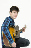 Teenager playing guitar. Wearing shirt isolated on white background Royalty Free Stock Images