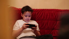 Teenager is playing his portable game console. stock footage
