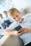 Teenager playing with smartphone at home Stock Photo