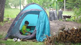 Teenager playing tablet. Teenager in a tent who is standing in the woods playing on the tablet stock video