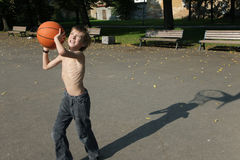 Teenager plays basketball in the street Royalty Free Stock Photo