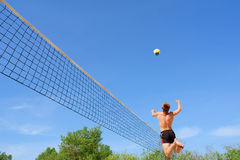 Teenager plays beach volleyball - high jump with strike Royalty Free Stock Image