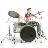 Teenager plays drums in studio with white background. Teenage caucasian boy plays drums in studio with white background Stock Photography