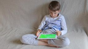 Teenager plays on tablet. Teenager sits and plays on the tablet stock video footage