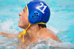 Teenager in Pool with Head Gear on. Teenage Boy in a waterpolo match showing Determination Stock Photo