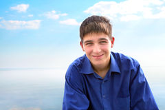 Teenager portrait. Smiling young man portrait on the sea background Royalty Free Stock Image
