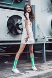 Teenager posing in white dress and green socks on the street. Streetstyle, fashion. Teenager posing in white dress and green socks on the street. Propellers on Stock Images