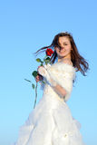 Teenager posing in white wedding dress with rose Royalty Free Stock Images