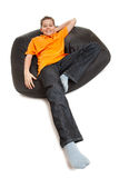 Teenager on pouffe Stock Image