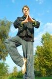 Teenager practising yoga. A teenage boy relaxing outdoors Stock Image