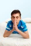 Teenager praying. Teenage boy lying casually on bed nd praying Stock Photos