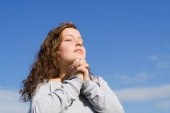 Teenager praying. Teen hands clasped  eyes closed praying Royalty Free Stock Photography