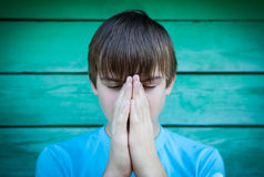 Teenager Praying outdoor. Vignetting Photo of Teenager praying on the Wooden Wall Background Stock Image