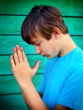 Teenager praying outdoor. Teenager praying on the Wooden Wall Background Stock Photos