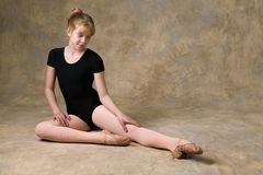 Teenager preparing for ballet. Teenage girl getting ready for ballet dance with warm-up exercises Royalty Free Stock Image