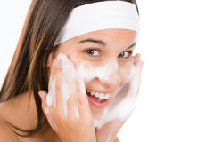 Teenager problem skin care - woman wash face. With cleansing foam Royalty Free Stock Images