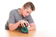 Teenager in professional training using grinding machine. In front of white background Royalty Free Stock Photos