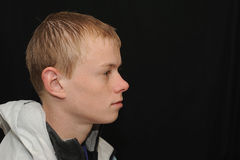 Teenager profile. A studio portrait of a young teenage model on a black background Stock Image