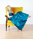 Teenager in prom dress. Pretty teenager sat in chair wearing blue prom dress, studio background Stock Photo