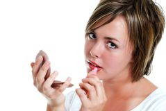 Teenager putting on lipstick Stock Image