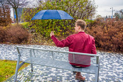 Teenager in rain after bad date with loved girlfriend. Teen boy sitting alone sad in rain after romantic date with girlfriend gone wrong before valentine stock images