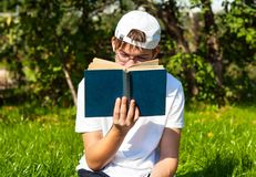 Teenager read a book. On the grass in the summer garden Royalty Free Stock Photography