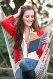 Teenager reading a book. A beautiful teenager sitting on a hammock reading a book Stock Photos